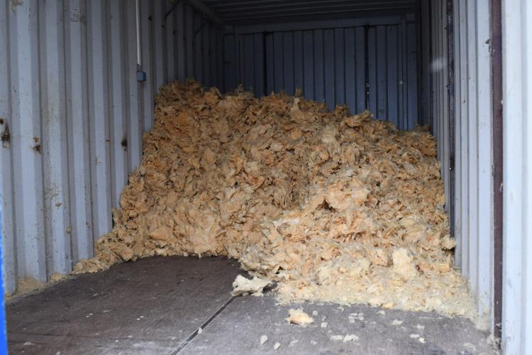 container fyldes med ødelagt mineraluld
